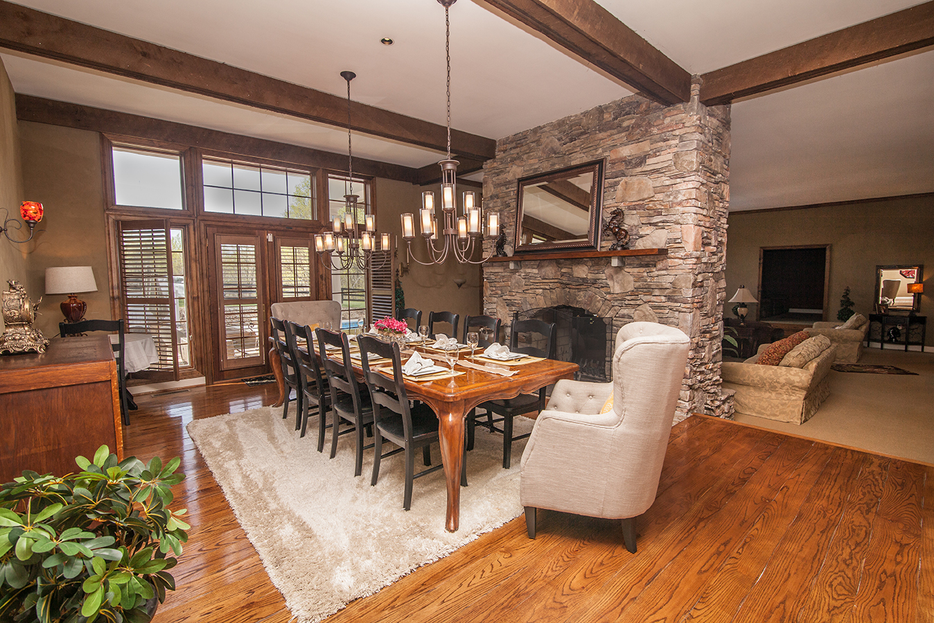 Lead To The Gracious Formal Dining Room 21 X 15 Featuring Hardwood Floors Beamed Ceiling Stone Fireplace And French Doors Opening Covered